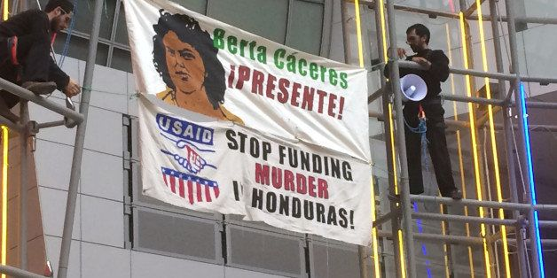 "Two men hold two banners which read ""Berta Cáceres Presente!"" and ""USAID STOP FUNDING MURDER HONDURAS"" in the atrium"