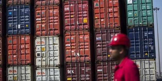 An Iranian safety inspector walks past stacked shipping containers at Shahid Rajaee port, some 20 kms west of Gulf port city