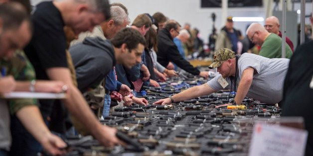 CHANTILLY, VA - OCTOBER 3: People look at handguns as thousands of customers and hundreds of dealers sell, show, and buy guns