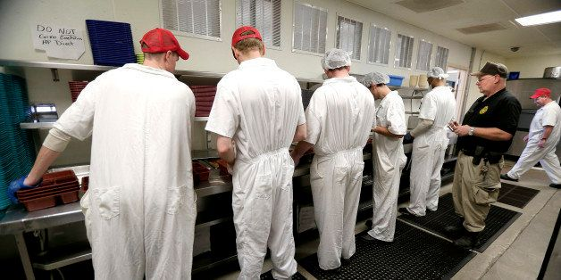 In this photo taken Tuesday, Dec. 8, 2015, corrections officer Kevin Cranston watches inmates working in the kitchen at the E