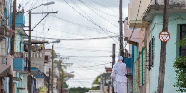 HAVANA, CUBA - 2015/09/19: Afro religious woman with crisscrossing overhead electric wires and a woman dressed in traditional