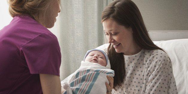 Caucasian mother holding newborn in hospital