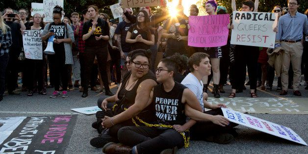Front from left, demonstrators Jess Jude, Loan Tran and Noah Rubin-Blose, sit chained together in the middle of the street du