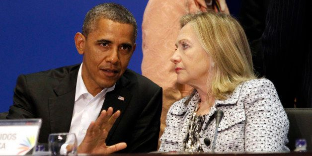 U.S. President Barack Obama and Secretary of State Hillary Clinton talk during the plenary session of the Summit of the Ameri