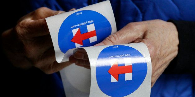 A Hillary Clinton supporter hands out stickers for her campaign during a Democratic caucus Saturday, March 26, 2016, in Seatt