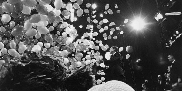 31st October 1968:  Republican presidential candidate Richard Nixon (1913-1994) is showered by balloons while standing on sta
