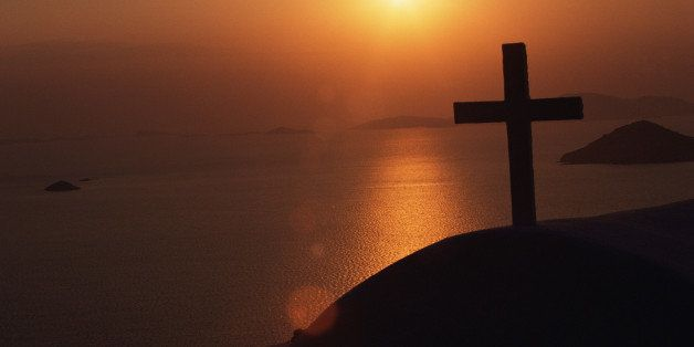 Silhouette of cross overlooking ocean at dusk