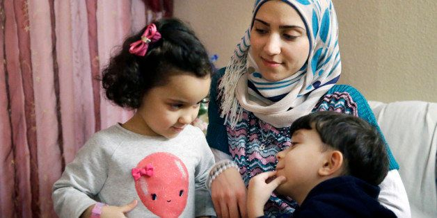 In this photo made Monday, Nov. 29, 2015, Syrian refugee Maryam al Jaddou, center, looks on as her children twins Maria, left
