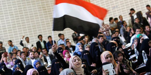 A Yemeni girl, center, waves her national flag as she chants slogans during a ceremony to mark the second anniversary of the