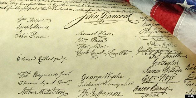 An American flag close-up and folded and place on the signatures on the Declaration of Independence.