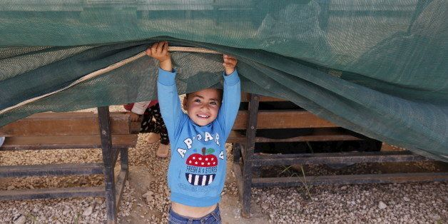 A Syrian child plays during a visit by actress Ashley Judd, U.N. Population Fund (UNFPA) Goodwill Ambassador, to Al Zaatari r