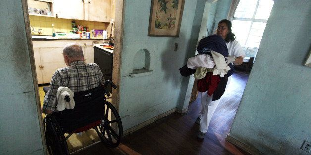 MIAMI - DECEMBER 14:  United HomeCare Services home health aide Wendys Cerrato carries bedding to the washing machine as she