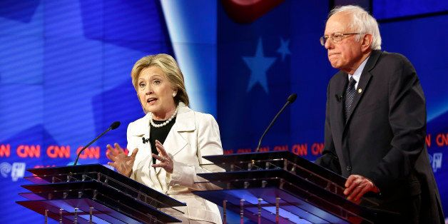 Democratic presidential candidates Sen. Bernie Sanders, I-Vt., right, listens as Hillary Clinton speaks during the CNN Democr