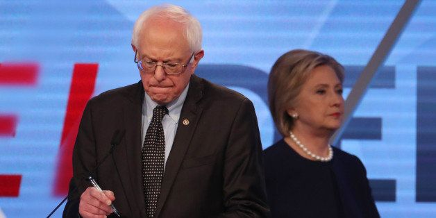 Democratic U.S. presidential candidate Senator Bernie Sanders writes on his notes as his rival Hillary Clinton walks behind h