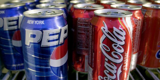Cans of Pepsi and Coke are shown in a news stand refrigerator display rack in New York Friday, April 22, 2005. (AP Photo/Mark