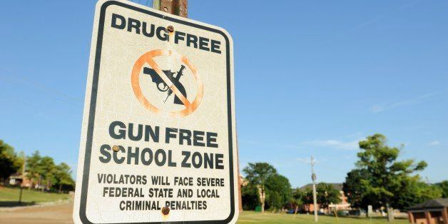 Drug and gun free school zone with violation sign.