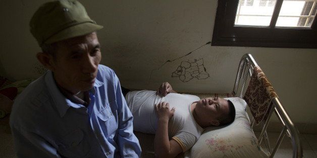 Nguyen Hong Phuc, a 63-year-old former soldier, sits on the bed with his son Nguyen Dinh Loc, 20, who is recovering from a re