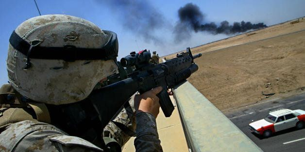 FALLUJAH, IRAQ:  An US soldier from 2nd Battalion, 1st Marines, takes position on a bridge over a highway inspecting a plume