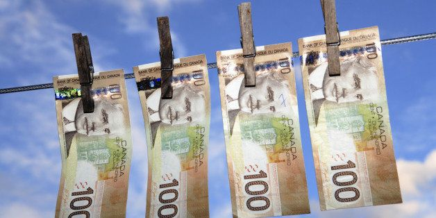 Canadian $100 banknotes hanging from a washing line - concept of money laundering. Note, banknotes have been altered from ori