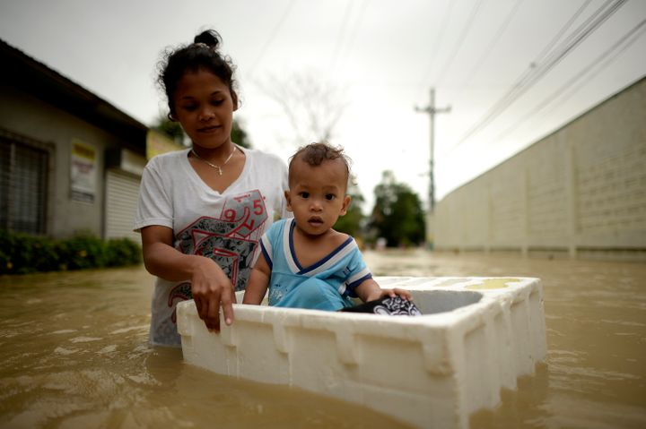 Lovelyn Cesar, 22, carries her one year old baby Matthew as she cross a flooded street in a suburb of Manila after two histor