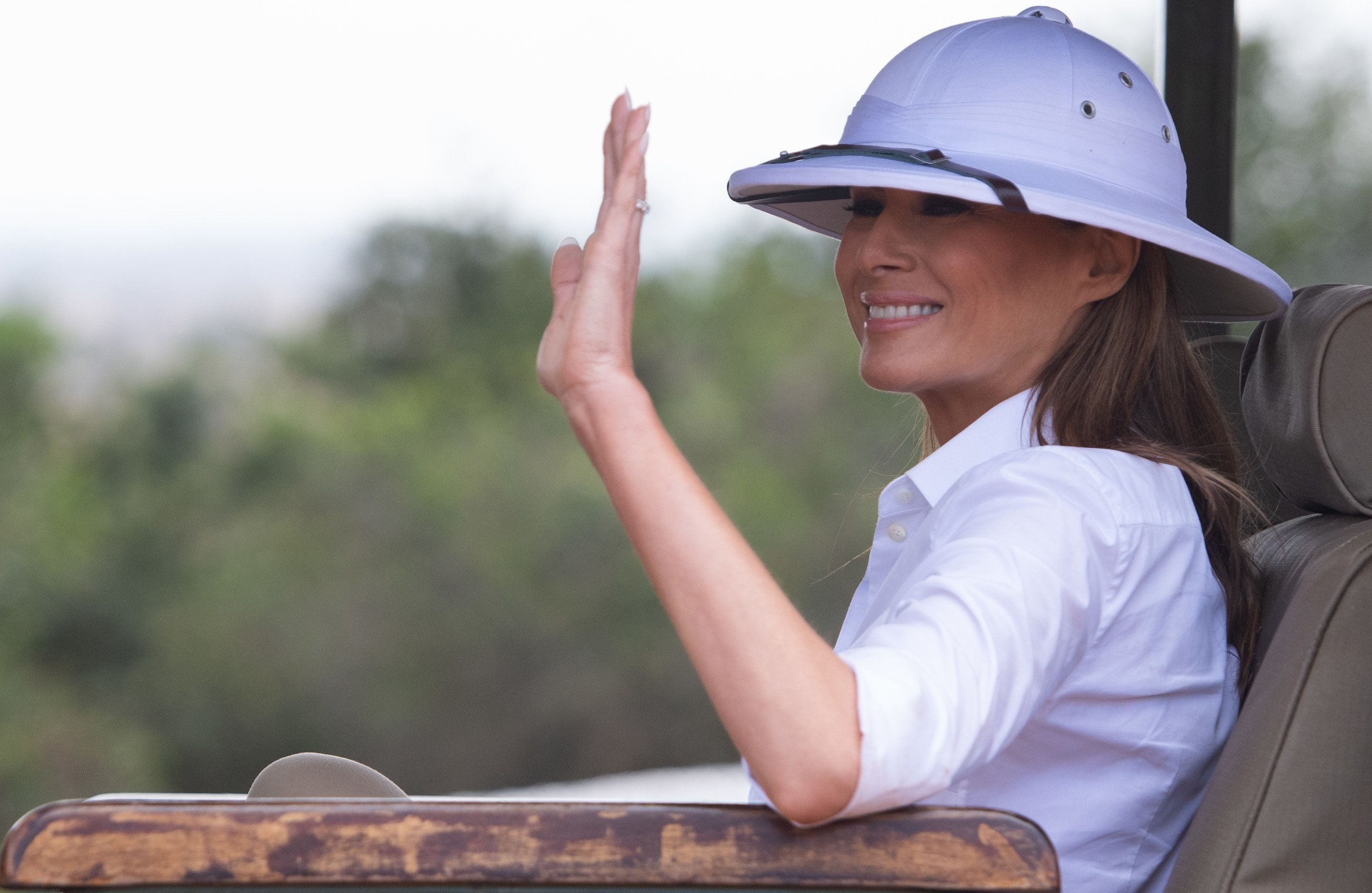 TOPSHOT - US First Lady Melania Trump waves as she travels in a vehicle while on a safari at The Nairobi National Park in Nairobi on October 5, 2018, as she pays a one day visit to the country during her solo tour of Africa promoting her children's welfare programme. (Photo by SAUL LOEB / AFP)        (Photo credit should read SAUL LOEB/AFP/Getty Images)