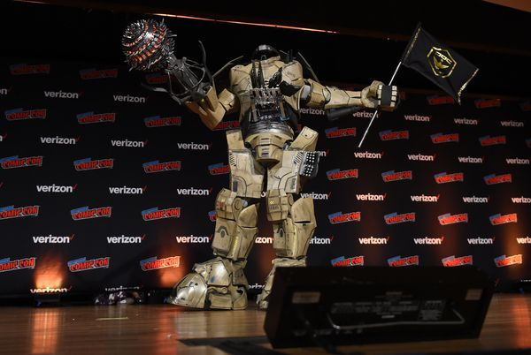 A fan shows off a massive robot outfit on stage.
