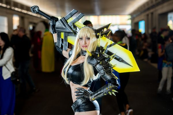 A cosplayer poses with a giant sword outside the Javits center.