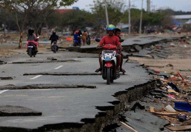 오토바이를 탄 주민들이 지진 및 쓰나미 피해를 입은 도로 위를 지나가는 모습. 팔루. 2018년
