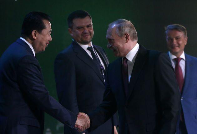 인터폴 총재 직을 사임한 멍훙웨이 중국 공안부 부부장이 지난 6월 모스크바에서 열린 국제사이버안보회의에서 블라디미르 푸틴 대통령과 악수하고