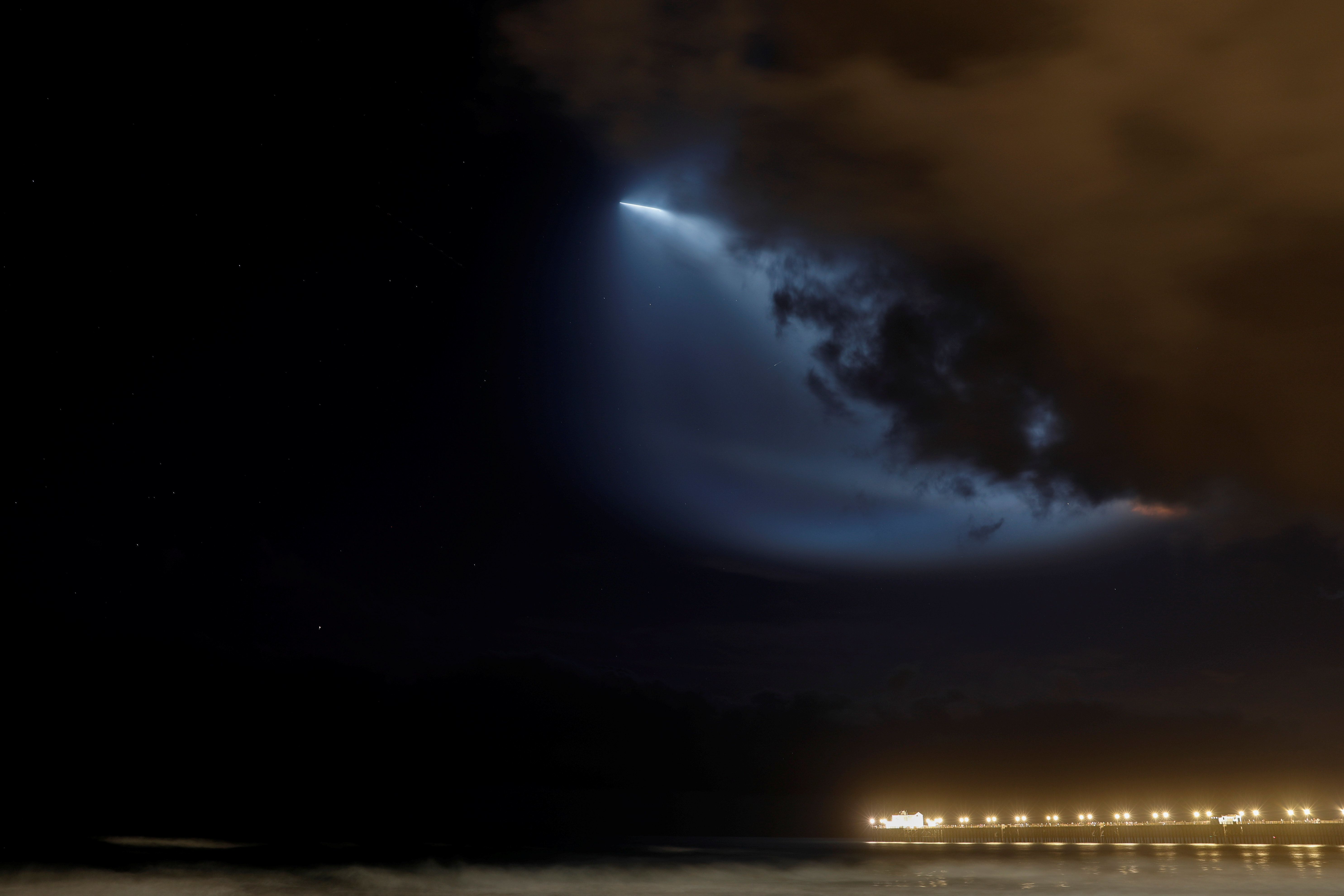 A SpaceX Falcon 9 rocket lights up the evening sky over Oceanside, California as it carries an Argentinian Earth-observing satellite into space after blasting off from Vandenberg Air Force Base, California, U.S., October 7, 2018.     REUTERS/Mike Blake