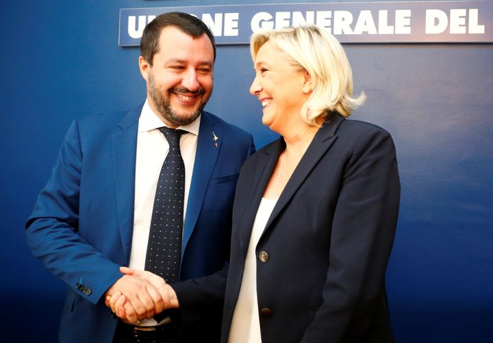 Marine Le Pen and Matteo Salvini shake hands before holding a news conference in Rome on Oct. 8.