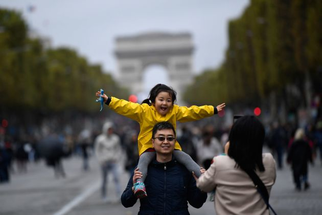 A family poses on the Champs-Elysées on a car-free day in Paris last