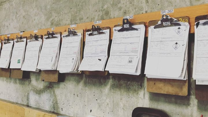 Clipboards with paper inspection sheets hang on the wall of a Washington State Department of Transportation maintenance offic