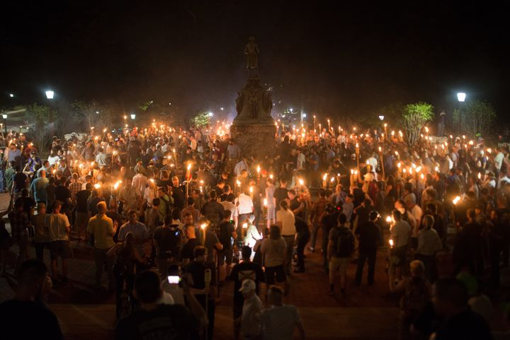 Neo-Nazis and white supremacists encircle counter protestors at the base of a statue of Thomas Jefferson after marching throu