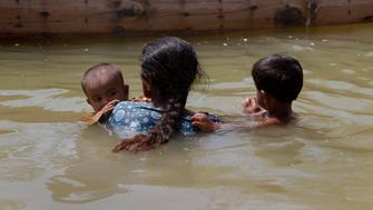 A woman displaced by flooding carries her children as she approaches a boat while returning to her flooded town of Bobak, about 300 kilometres (186 miles) from Karachi on September 20, 2010. REUTERS/Akhtar Soomro (PAKISTAN - Tags: DISASTER ENVIRONMENT)