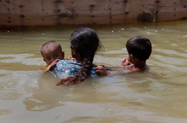A woman displaced by flooding carries her children to a boat as they return to Bobak, Pakistan, in 2010.AnIntergovernmental...