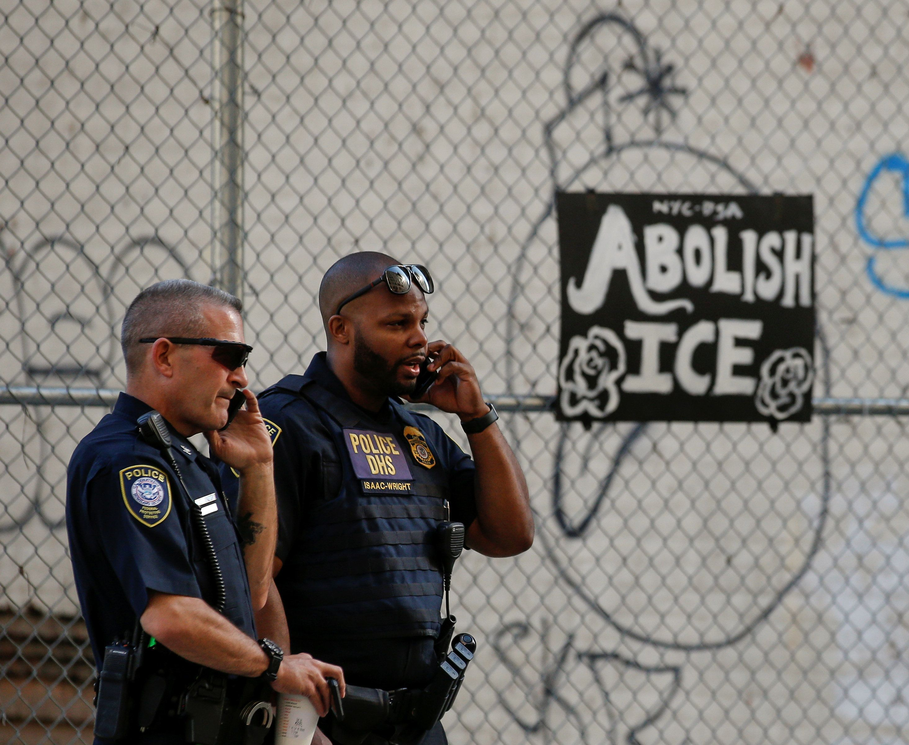 Department of Homeland Security officers  watch members of Occupy ICE, a group set on disrupting Immigration and Customs Enforcement (ICE) operations, outside the ICE offices in New York City, U.S., June 25, 2018. REUTERS/Brendan McDermid