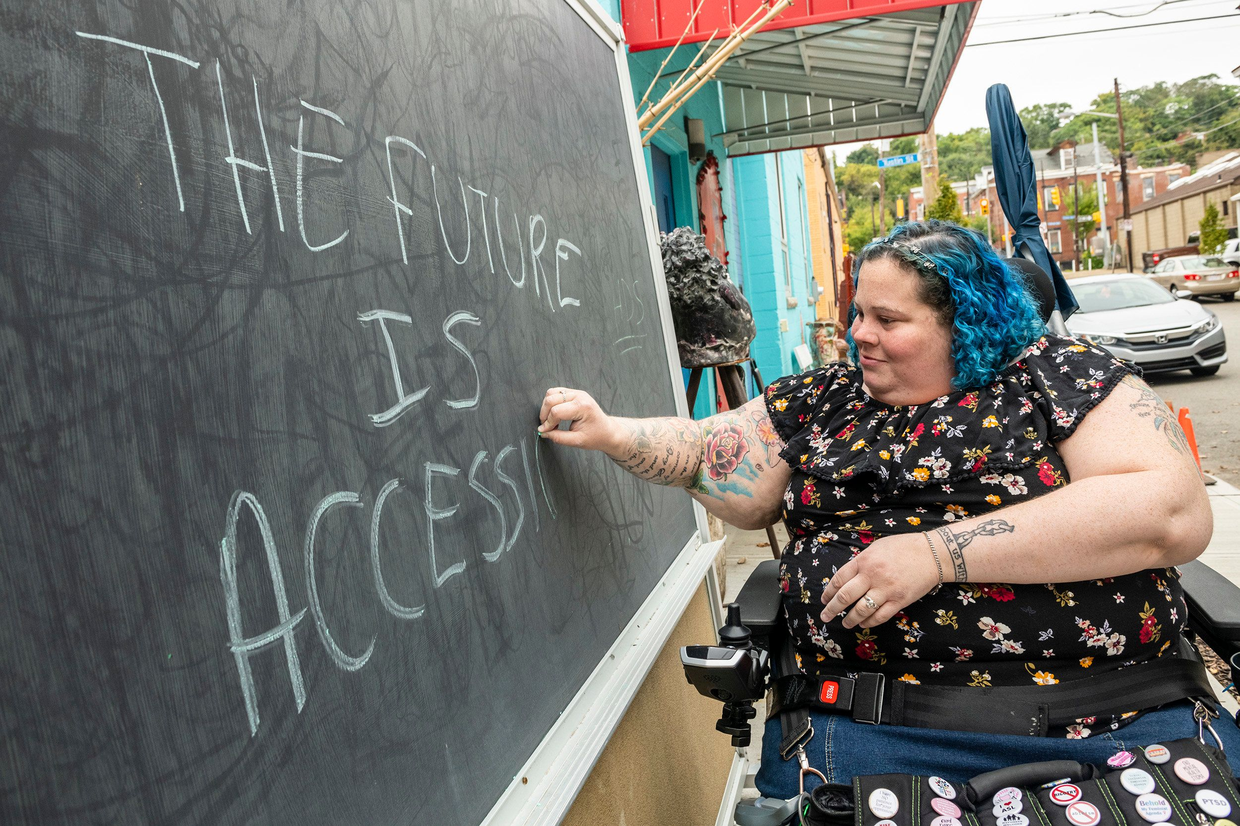 "Alisa writes ""The Future is Accessible"" on a chalkboard of a neighborhood business."