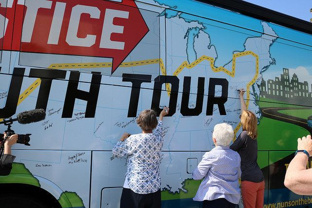 People sign the Network Lobby bus that will be heading to 21 states over the course of 27 days.