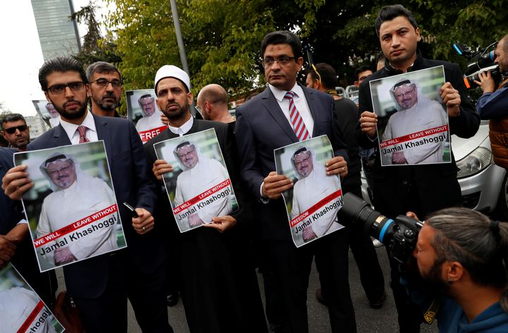 Human rights activists and friends of Saudi journalist Jamal Khashoggi hold his pictures during a protest outside the Saudi C