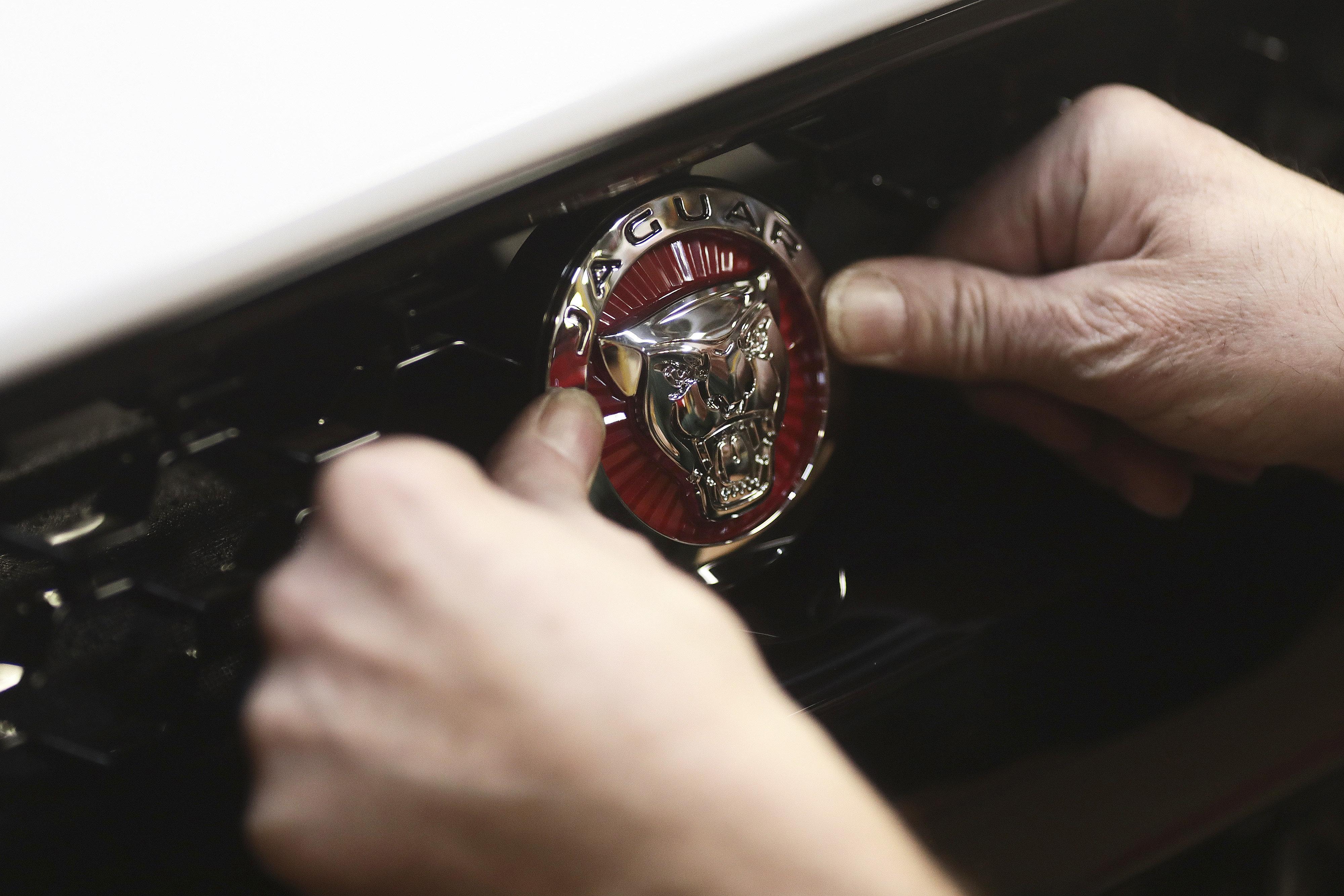 영국 버밍엄 인근 캐슬 브롬위치에 위치한 재규어 공장에서 한 노동자가 생산라인을 막 빠져나온 재규어 F-타입 차량의 전면 로고 위치를 수정하고 있다. 20017년 3월16일.