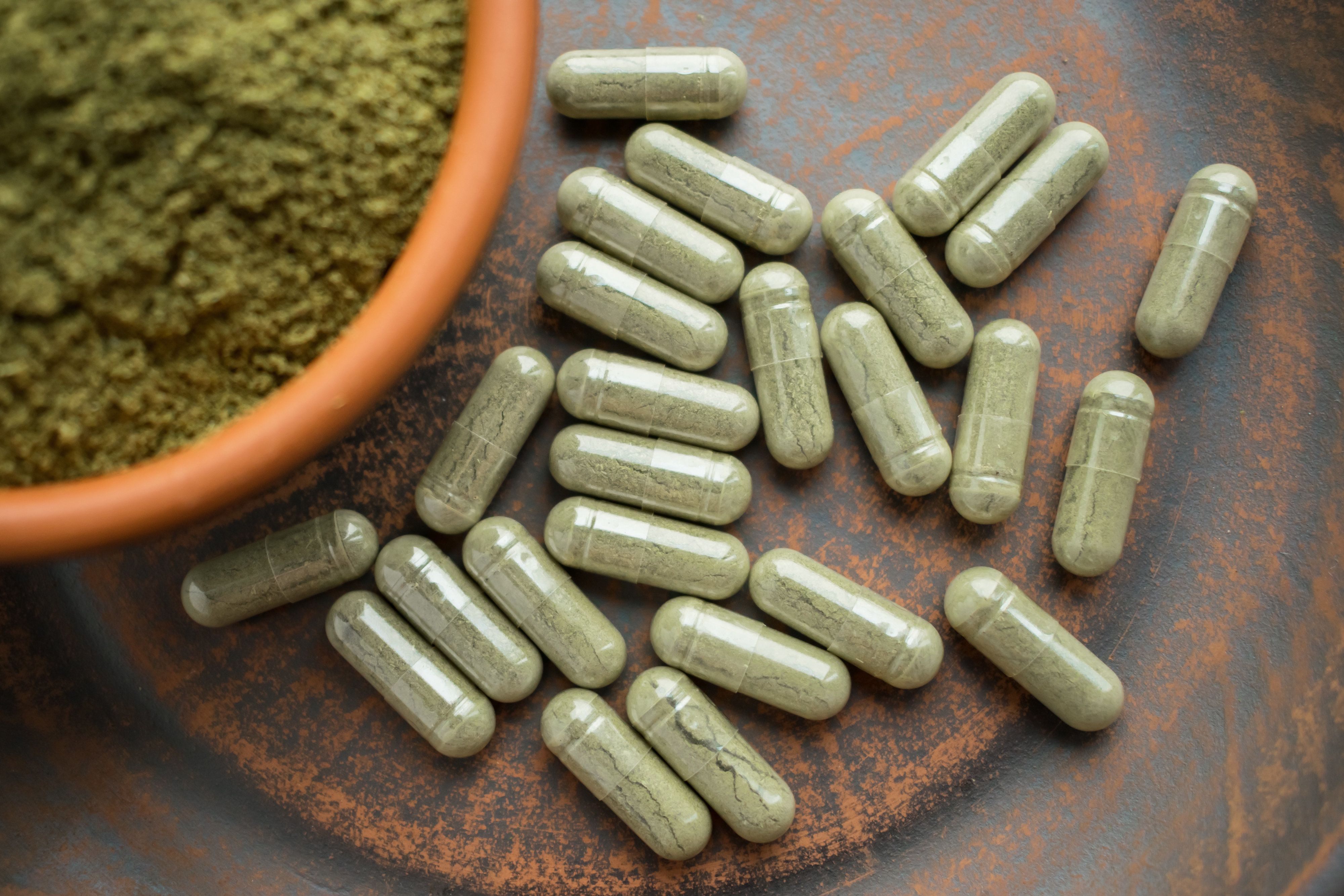 Kratom powder and capsules are seen on a table. Ohio is seeking to ban the popular herbal supplement based on a series of dis