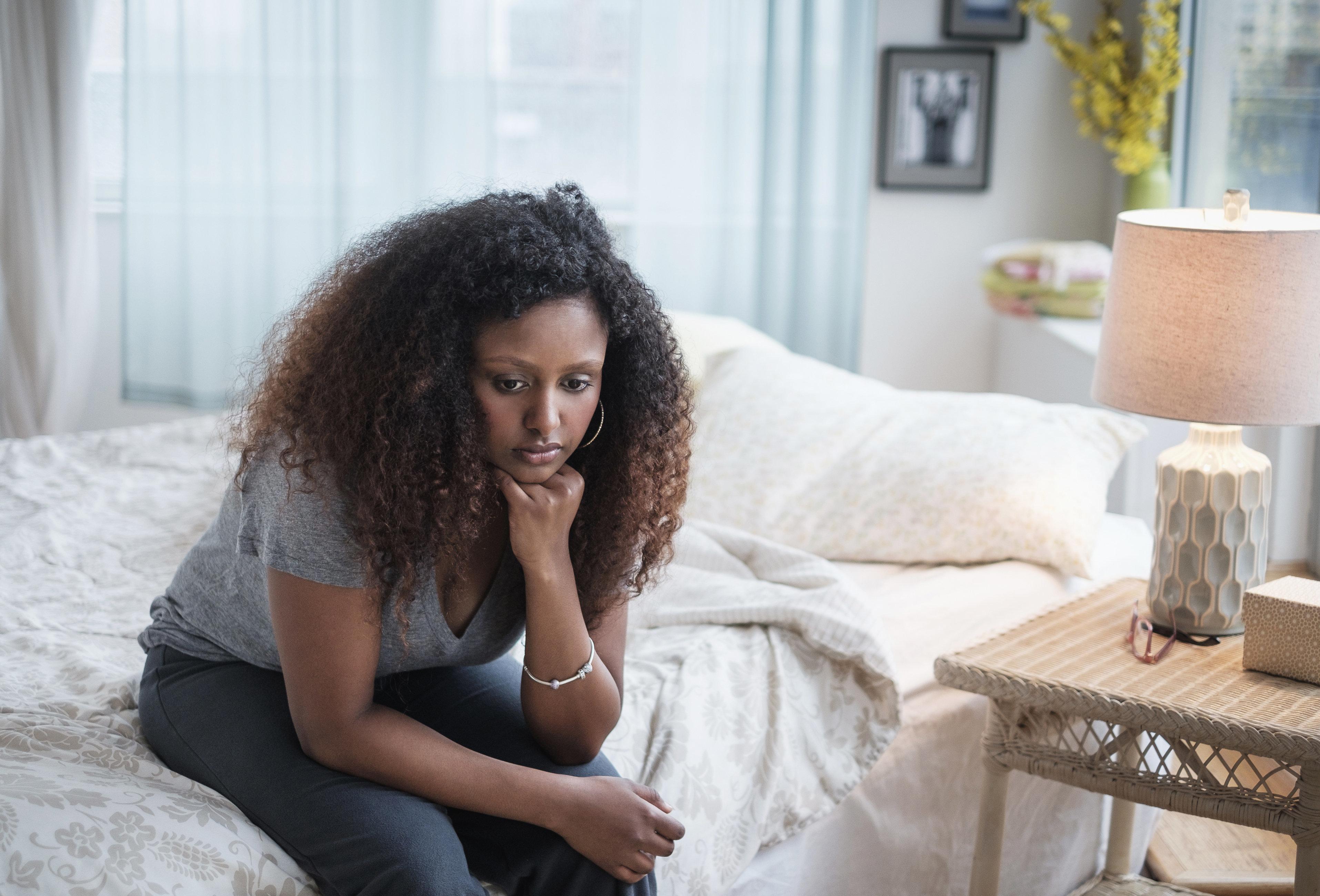 Sad Black woman sitting on bed