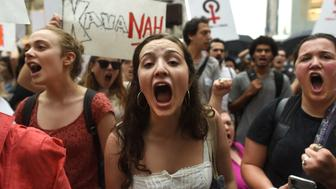 TOPSHOT - Women hold a  protest in front of Trump Tower in New York on October 4, 2018 against Supreme Court nominee Brett Kavanaugh. - Top Republicans voiced confidence Thursday that Brett Kavanaugh will be confirmed to the US Supreme Court this weekend, as they asserted that an FBI probe had found nothing to support sex assault allegations against Donald Trump's nominee.'Judge Kavanaugh should be confirmed on Saturday,' Senator Chuck Grassley of Iowa, the chairman of the Senate Judiciary Committee, told reporters. (Photo by TIMOTHY A. CLARY / AFP)        (Photo credit should read TIMOTHY A. CLARY/AFP/Getty Images)