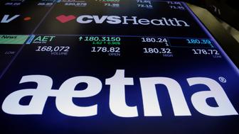 Logos of CVS and Aetna are displayed on a monitor above the floor of the New York Stock Exchange shortly after the opening bell in New York, U.S., December 5, 2017.  REUTERS/Lucas Jackson