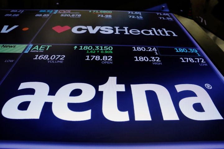 Logos of CVS and Aetna are displayed on a monitor above the floor of the New York Stock Exchange shortly after the opening be