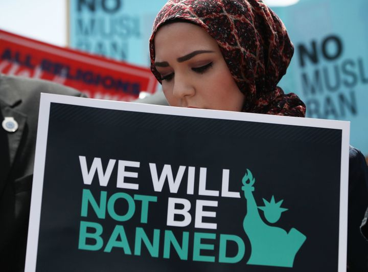 A woman participates in a demonstration against President Donald Trump's travel ban outside the U.S. Supreme Court following