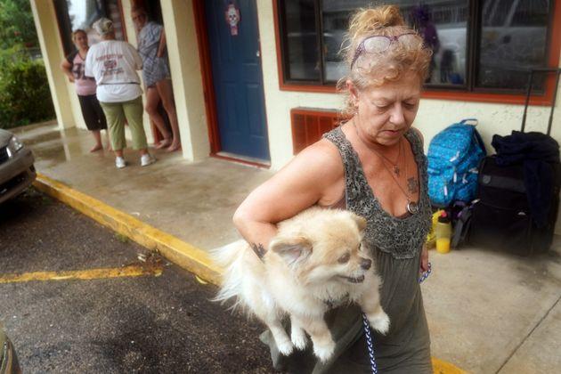 Lenora Adams lsostiene a su perro durante la evacuación en Panacea,
