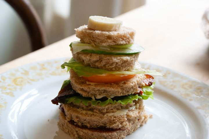 Russian Club Sandwich as described in a recipe in Bee Wilson's <i>Sandwiches: A Global History</i>. Club sandwiches are classically attributed to Americans but this Russian club features rounds of bread in descending height with jam, cream cheese and butter, in addition to classic club ingredients like bacon, lettuce and tomato.
