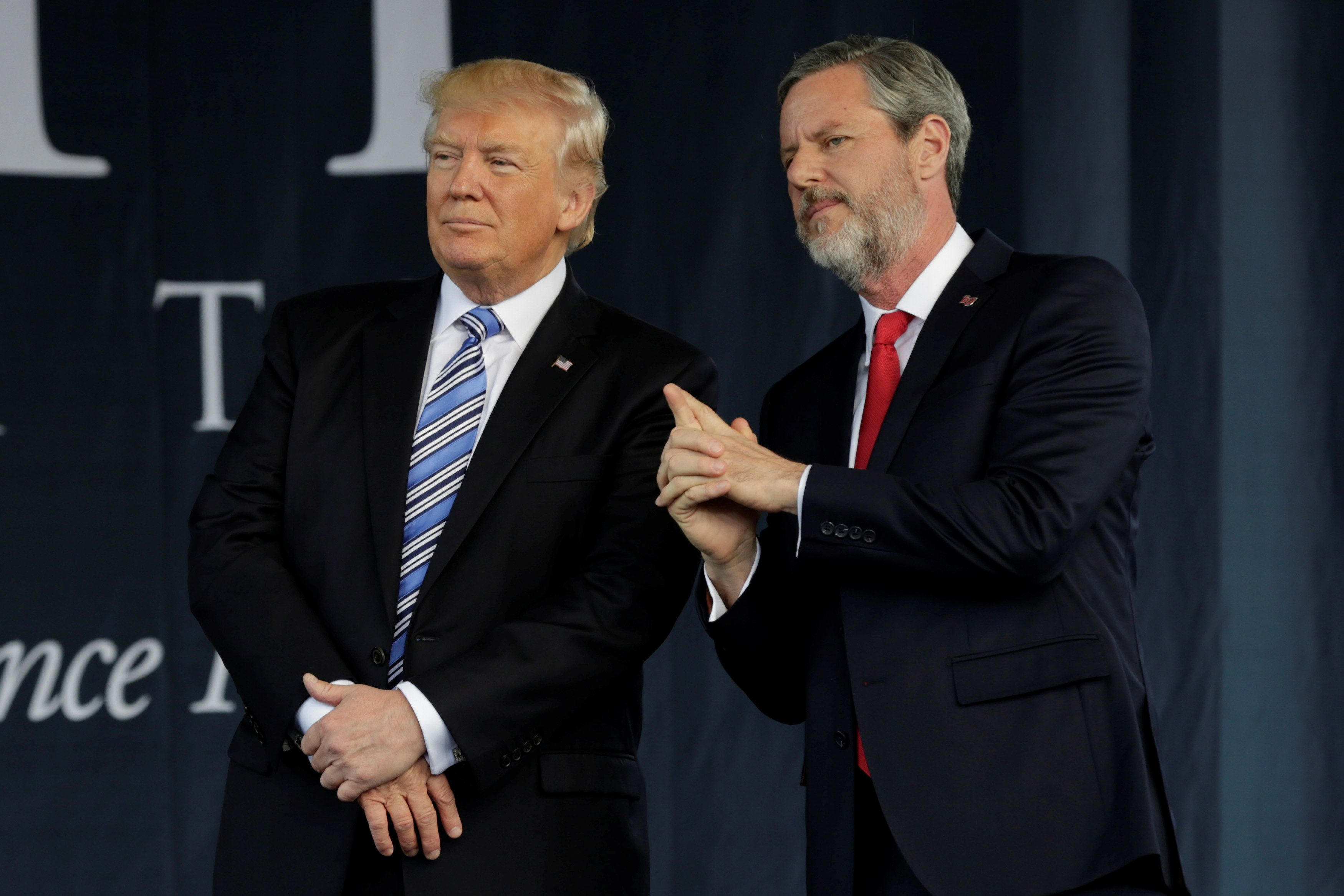 President Donald Trump stands with Liberty University's President Jerry Falwell Jr. after delivering a commencement speech th